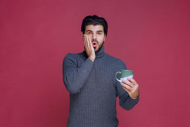 Homem de suéter cinza segurando uma caneca e pensando.
