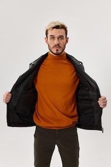Homem de suéter laranja e jaqueta desabotoada em uma visão recortada de retrato louro de fundo claro