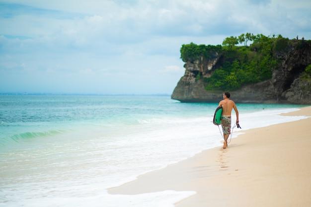 Homem de surf com prancha de surf, caminhando na praia tropical. estilo de vida saudável, atividades aquáticas