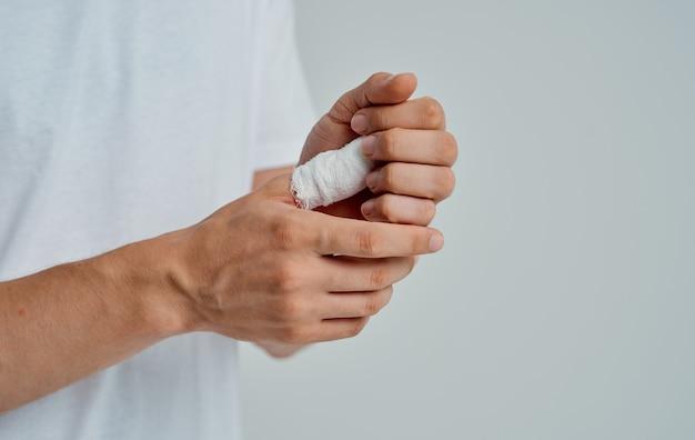 Homem de t-shirt branca enfaixado polegar remédio de problemas de saúde. foto de alta qualidade
