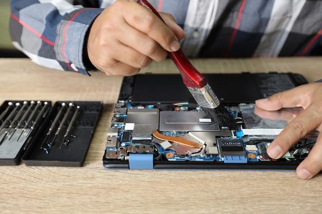 Homem de técnico usando uma escova de varredura para limpar o computador portátil