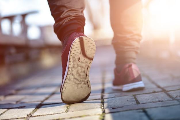 Homem de tênis caminhando na rua em um dia ensolarado