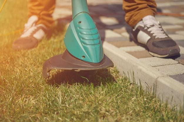Homem de tênis e calça está cortando grama verde com um moderno cortador de grama portátil em seu jardim ...