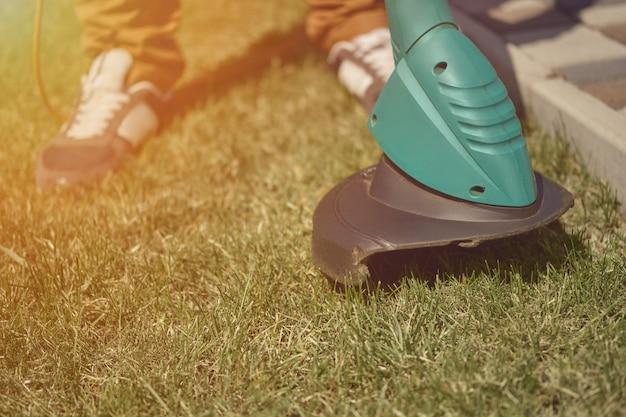 Homem de tênis e calças está cortando a grama verde com o cortador de grama elétrico portátil em seu quintal.