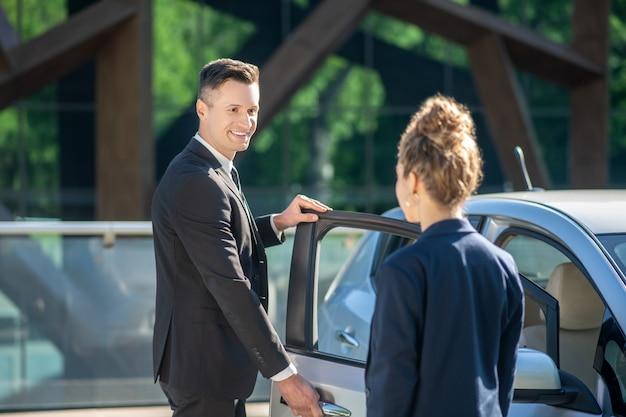 Homem de terno, abrindo a porta do carro, mulher em pé com as costas