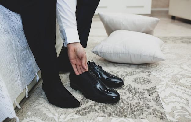 Homem de terno amarra cadarços em sapatos elegantes clássicos pretos.