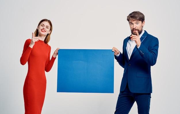 Homem de terno ao lado da mulher de vestido vermelho, modelo de anúncio de apresentação de maquete azul
