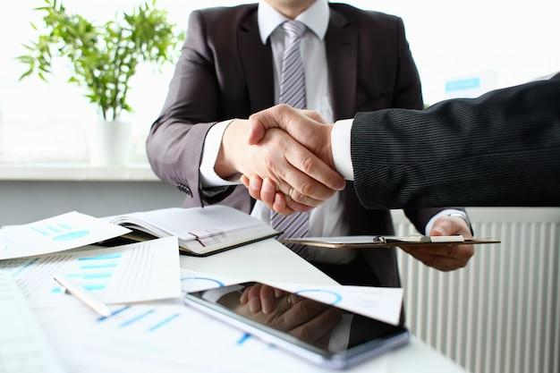 Homem de terno, apertando a mão como saudação no escritório