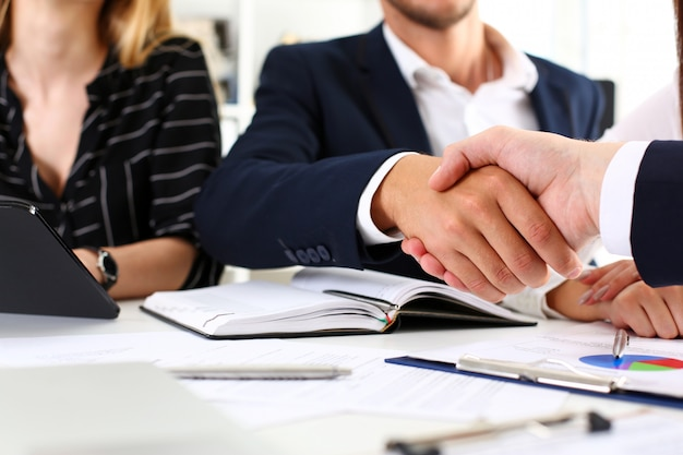 Homem de terno apertar a mão como olá no escritório closeup