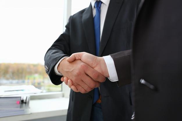Homem de terno apertar a mão como olá no escritório