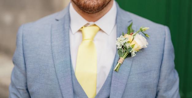 Homem de terno azul, camisa branca e gravata amarela
