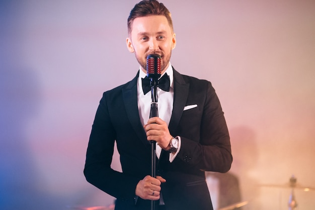 Homem de terno cantando no palco