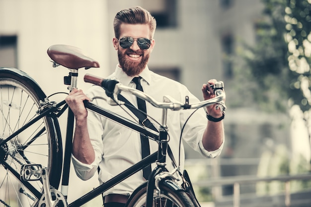 Homem de terno clássico e óculos de sol está carregando sua bicicleta.
