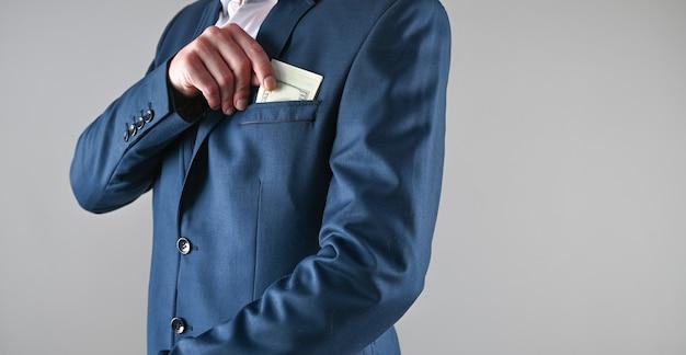 Homem de terno coloca dinheiro no bolso, conceito de corrupção