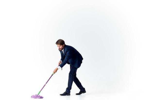 Homem de terno com um esfregão nas mãos as emoções da limpeza oficial