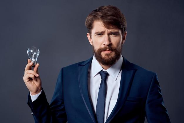 Homem de terno com uma lâmpada nas mãos, a ideia de emoções de sucesso. foto de alta qualidade