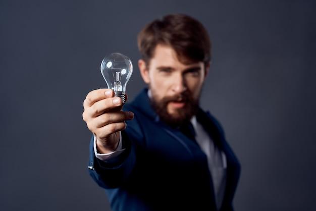 Homem de terno com uma lâmpada nas mãos, ideia de emoções de sucesso