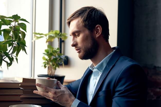 Homem de terno com uma xícara de café nas mãos, café da manhã, estilo de vida, lazer