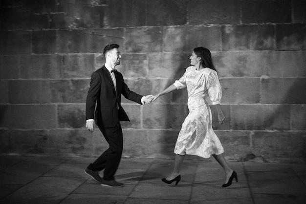 Homem de terno dançando com mulher na rua de noite