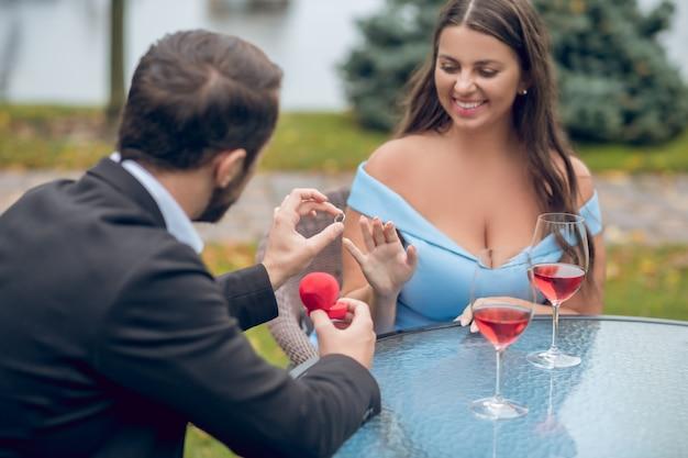 Homem de terno de costas para a câmera colocando o anel no dedo de sua amada mulher feliz sentada à mesa ao ar livre