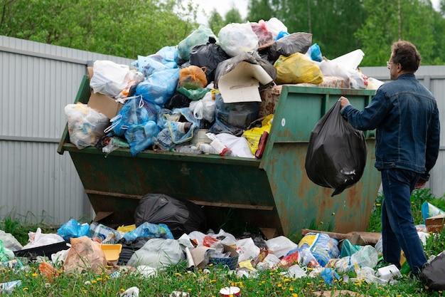 Homem de terno de jeans joga um saco plástico com um lixo em um contêiner de lixo ao ar livre no campo