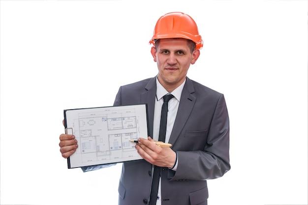 Homem de terno e capacete apontando para a planta da casa