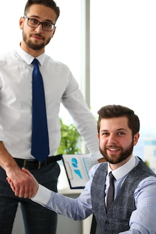 Homem de terno e gravata dando a mão para cumprimentá-lo no escritório