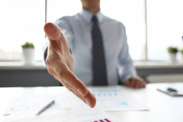 Homem de terno e gravata dar mão como olá no escritório closeup
