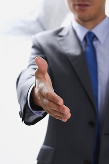 Homem de terno e gravata dar mão como olá