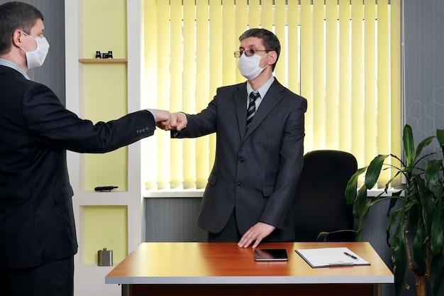 Homem de terno e máscara médica se levantou da mesa para dar as boas-vindas a outro que entrou