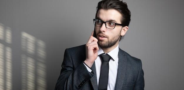 Homem de terno e óculos falando ao telefone em uma parede cinza