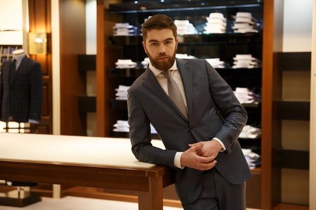 Homem de terno em pé perto da loja de mesa
