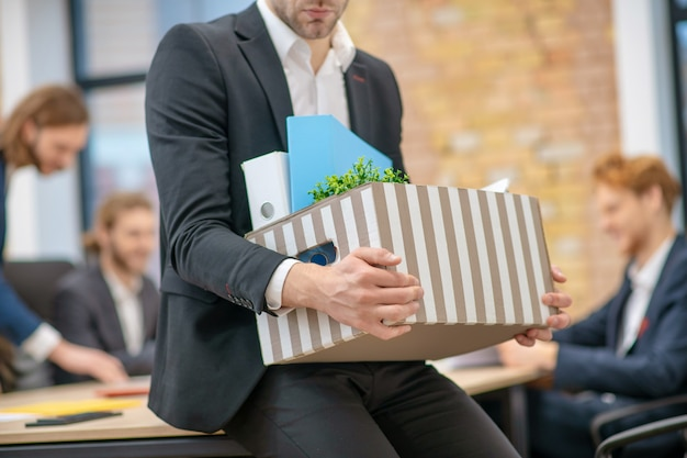 Homem de terno escuro com caixa listrada nas mãos, sentado no escritório, sem rosto visível