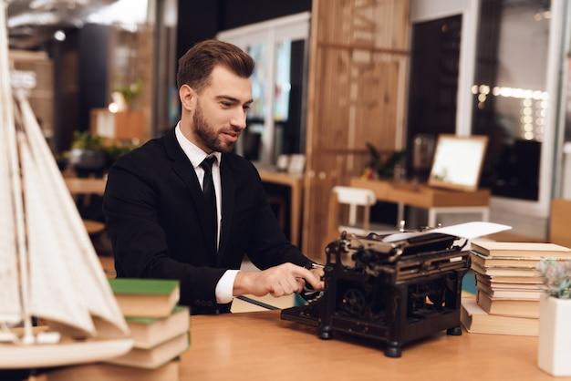 Homem de terno está sentado à mesa com uma velha máquina de escrever.