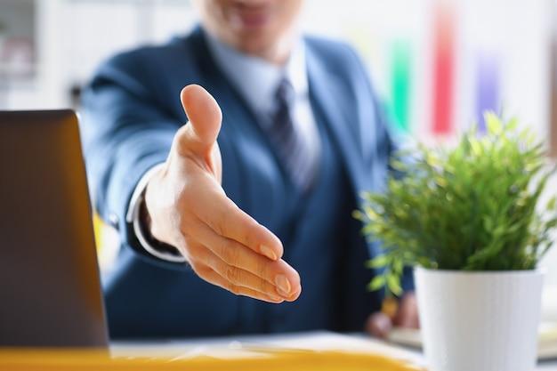 Homem de terno estendendo a mão para um close do aperto de mão