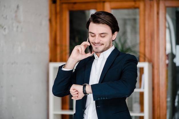Homem de terno fala ao telefone e verifica o relógio