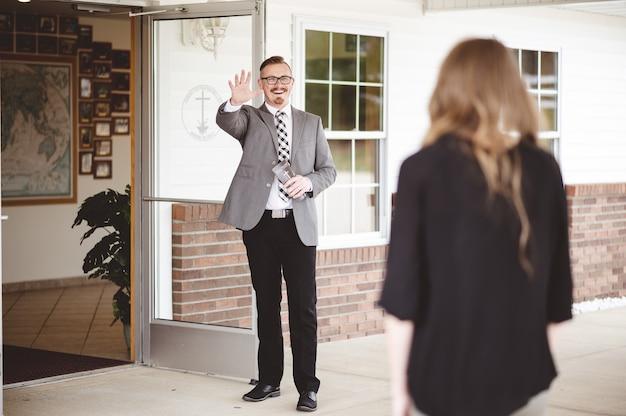 Homem de terno fora de uma igreja acenando e dando as boas-vindas a uma mulher