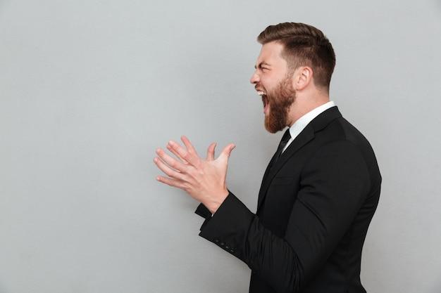 Homem de terno gritando e gesticulando com as mãos