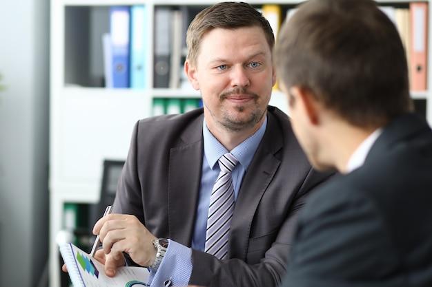 Homem de terno mostra gráfico com caneta no documento em reunião com clientes em retrato de escritório