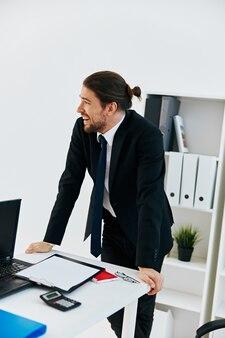 Homem de terno no escritório com tecnologias de documentos