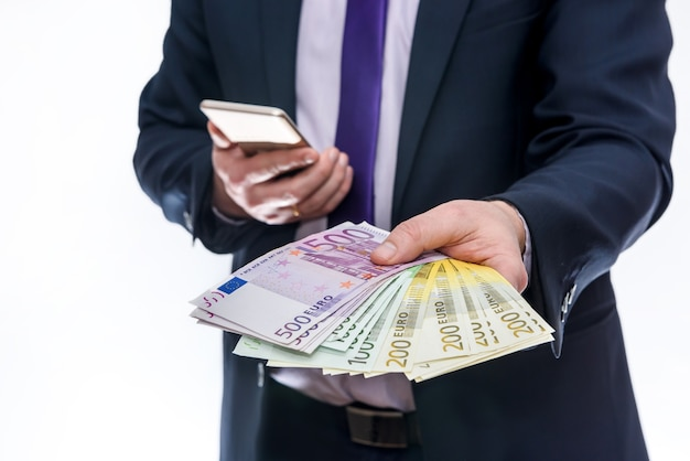 Homem de terno oferecendo notas de euro isoladas em branco