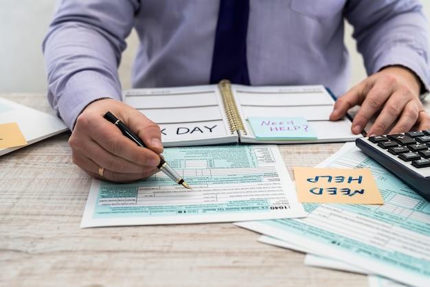 Homem de terno preenche o formulário fiscal 1040 individual dos estados unidos. hora do imposto. conceito de contabilidade