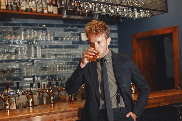 Homem de terno preto bebe álcool. um cara atraente bebe uísque em um copo.