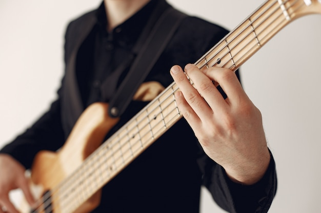 Homem de terno preto em pé com uma guitarra
