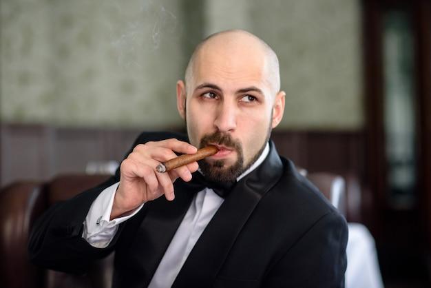 Homem de terno preto fuma um charuto