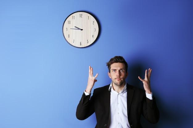 Homem de terno preto parado ao lado de um grande relógio na parede azul