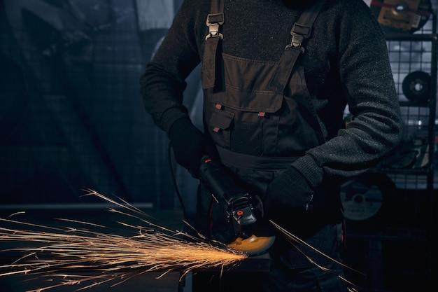 Homem de terno preto polindo metal com rebarbadora