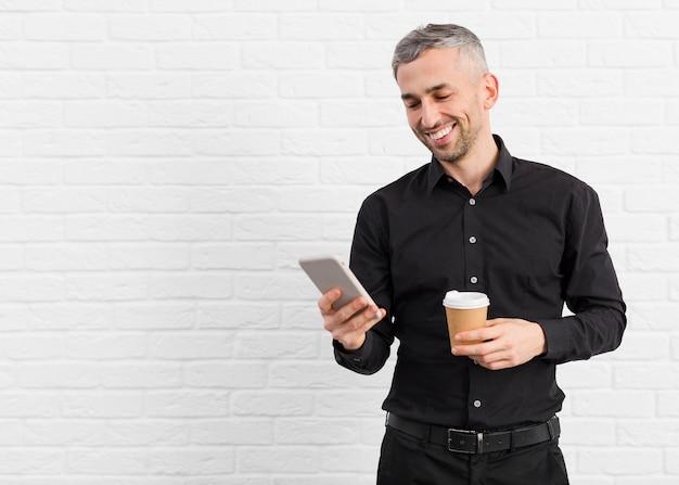 Homem de terno preto, segurando o telefone e café