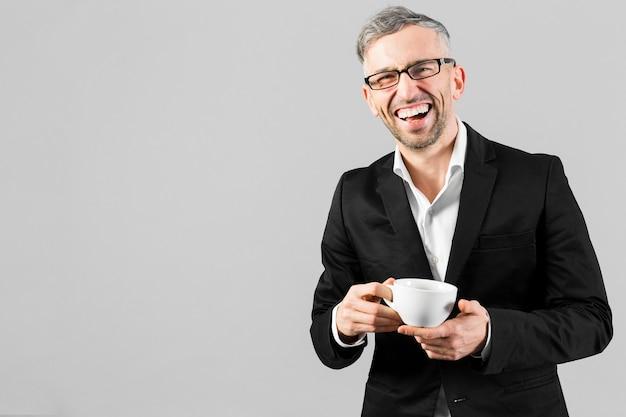 Homem de terno preto, segurando uma xícara de café e sorrisos