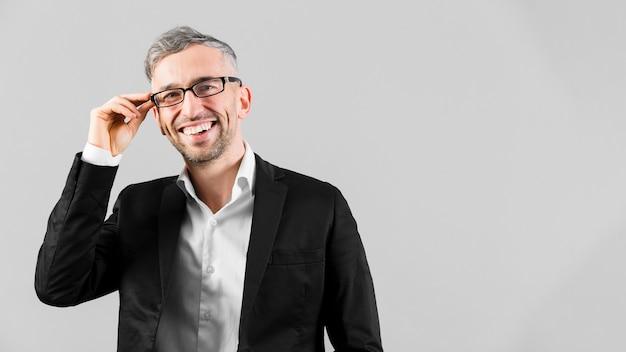 Homem de terno preto, usando óculos e sorrisos